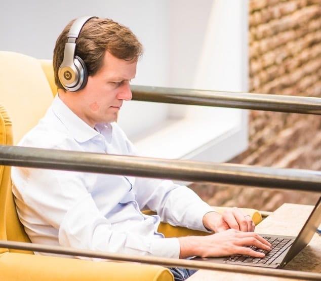 Un homme écoute une leçon au casque via son ordinateur