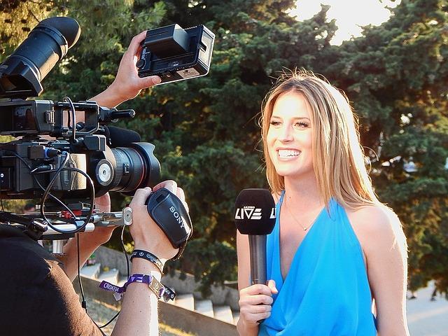 Femme journaliste devant des caméras et appareils photos