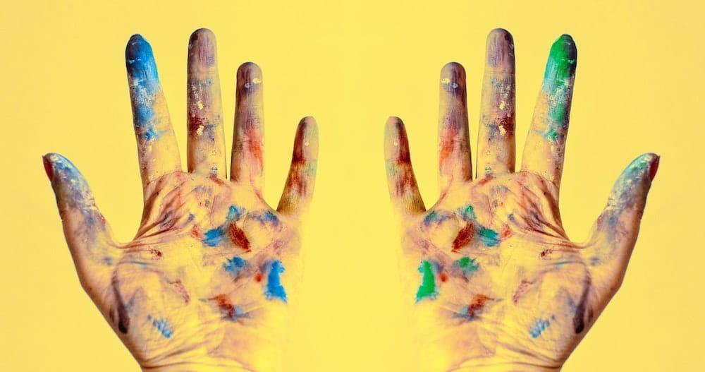 Mains couvertes de tâches de peintures sur un fond jaune