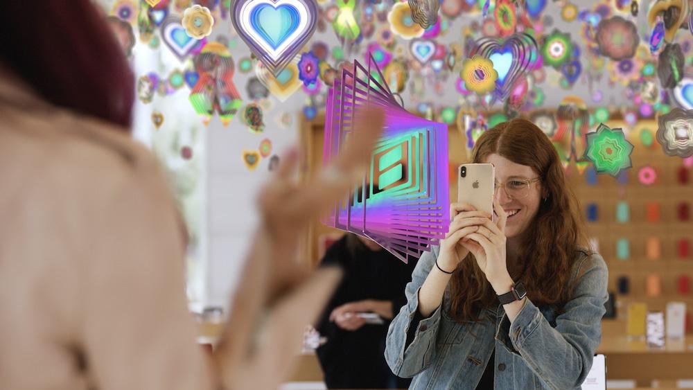 Femme faisant l'expérience d'une oeuvre d'art virtuelle dans un magasin Apple