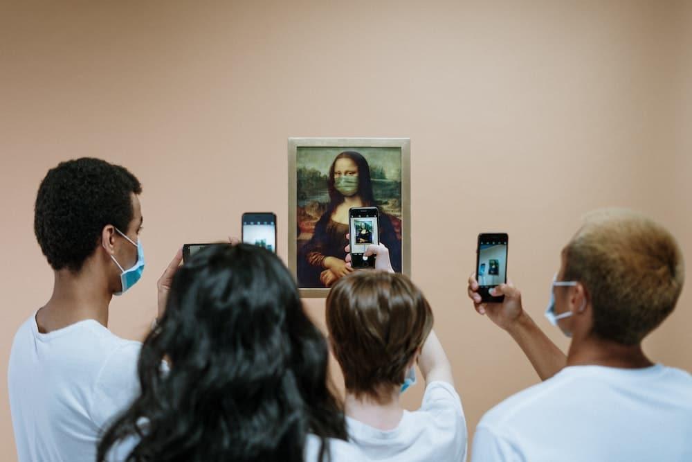 Touristes avec masques anti coronavirus prenant en photo Mona Lisa masquée