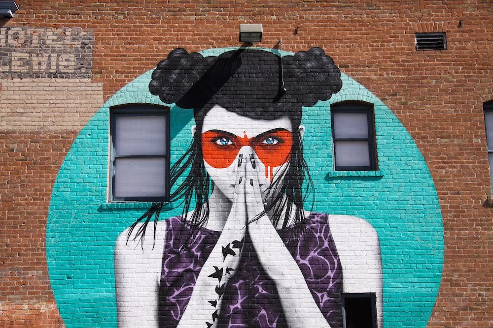 Femme peinte sur un mur de briques