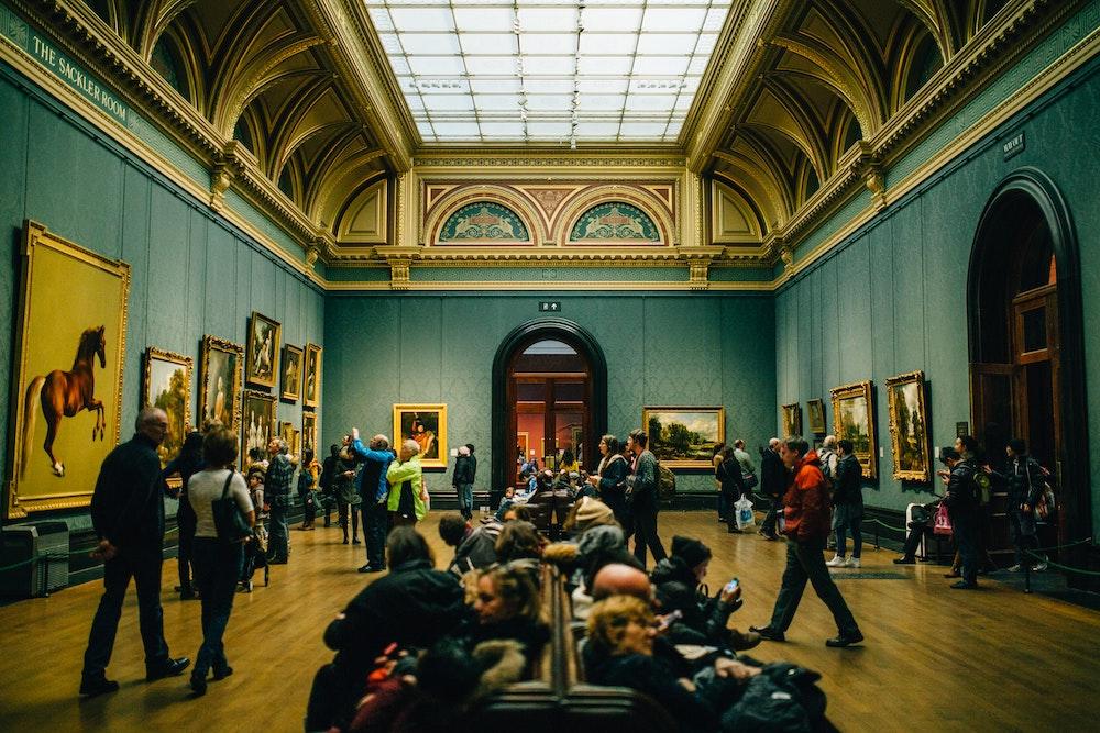 Salle d'un musée avec ses visiteurs découvrant des peintures