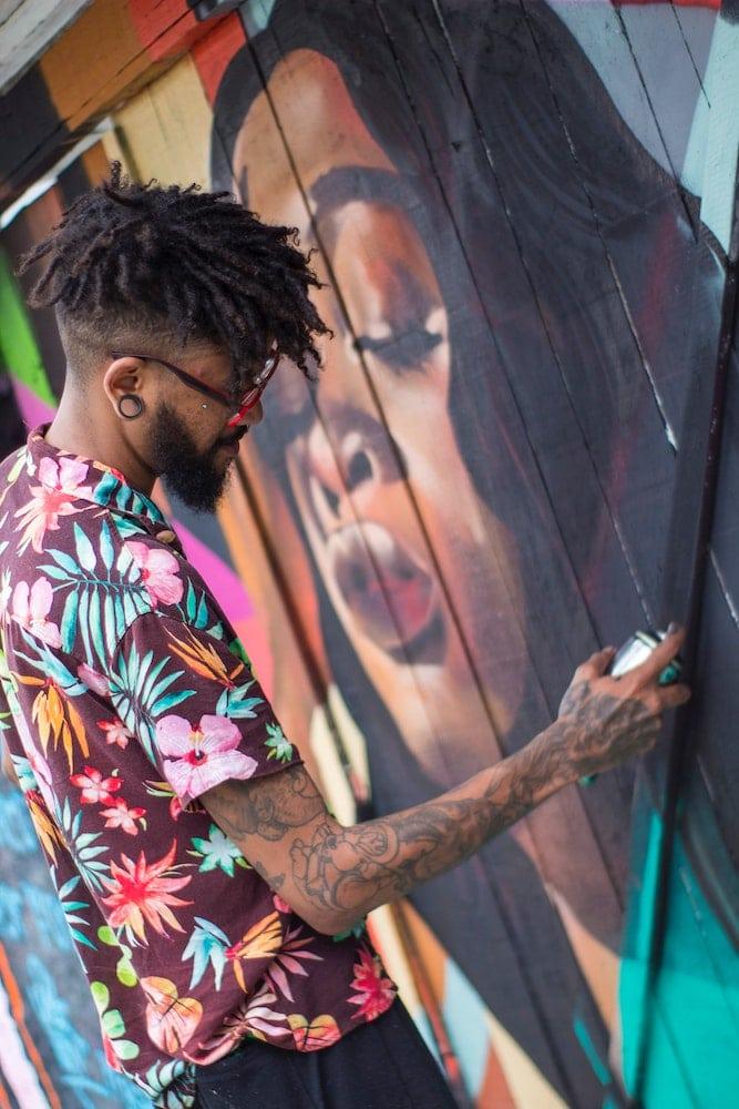 Street artiste en train de passer de la peinture en bombe sur le portrait d'une femme