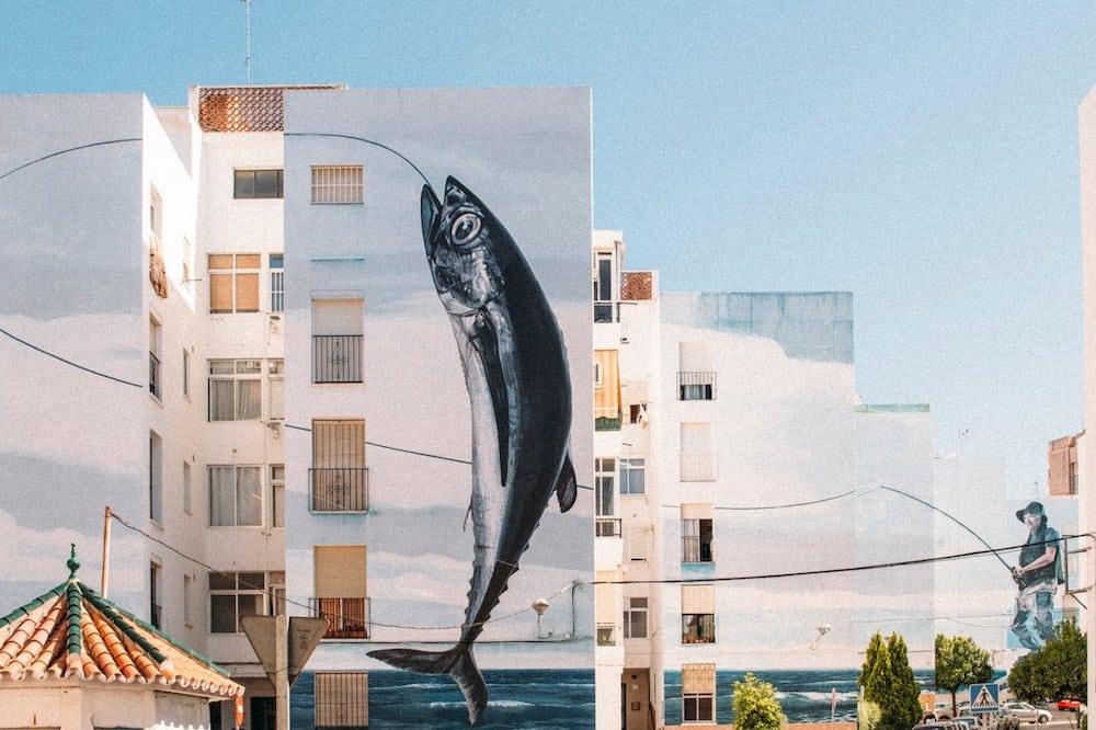 Fresque murale sur plusieurs immeubles : pêcheur à la ligne venant de prendre un poisson