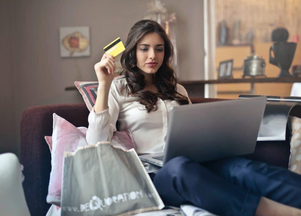 Jeune femme avec une carte de crédit en main pour fair un achat sur internet